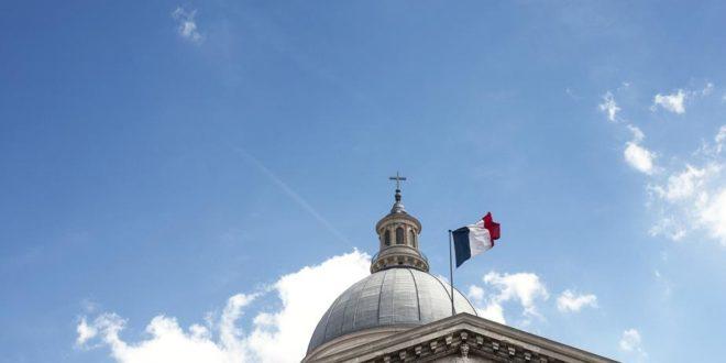 drapeau français flottant au dessus d'un bâtiment historique